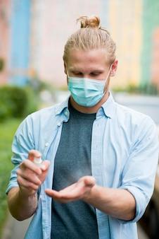Vista frontale dell'uomo con la maschera per il viso con disinfettante per le mani
