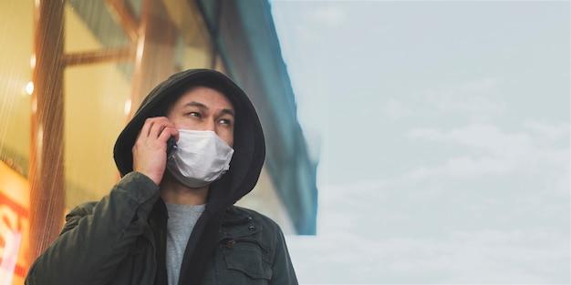 Vista frontale dell'uomo con la mascherina medica che comunica sul telefono