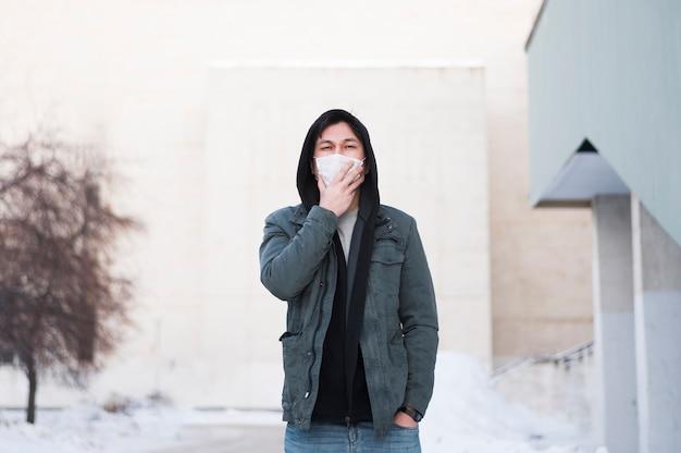 Vista frontale dell'uomo con la mascherina medica che propone all'esterno
