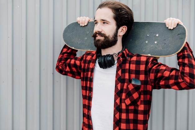 Vista frontale dell'uomo con lo skateboard