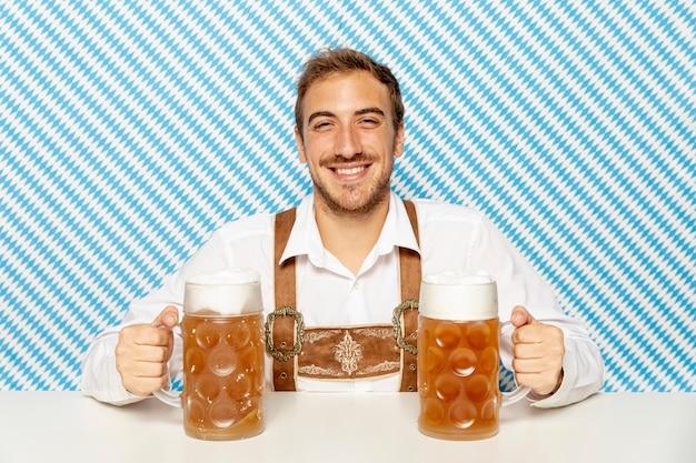 Vista frontale dell'uomo con pinte di birra