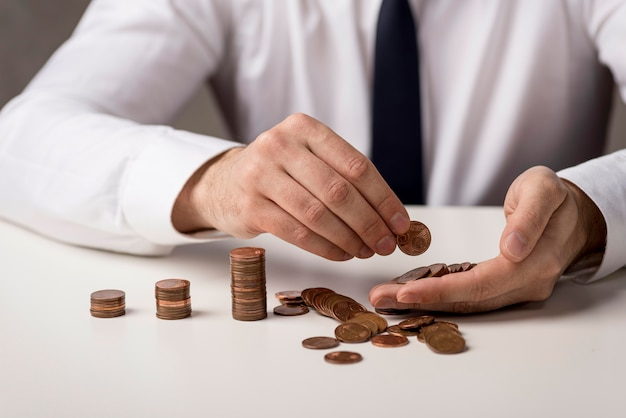 Vista frontale dell'uomo d'affari defocused con le monete