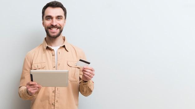 Vista frontale dell'uomo di smiley che compera online con la carta di credito