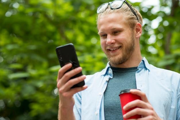 Vista frontale dell'uomo di smiley che parla sul telefono