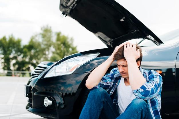 Vista frontale dell'uomo e auto nera