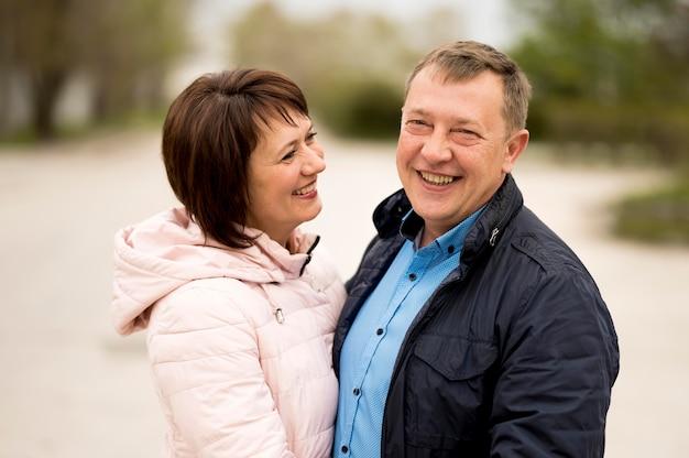 Vista frontale dell'uomo e della donna sorridenti in parco