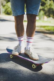 Vista frontale dell'uomo in piedi su skateboard
