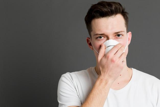 Vista frontale dell'uomo malato che indossa una maschera medica