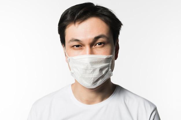 Vista frontale dell'uomo malato che posa con la maschera medica sopra