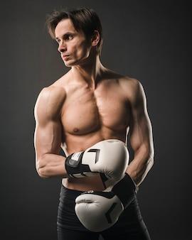 Vista frontale dell'uomo muscolare senza camicia che posa con i guantoni da pugile