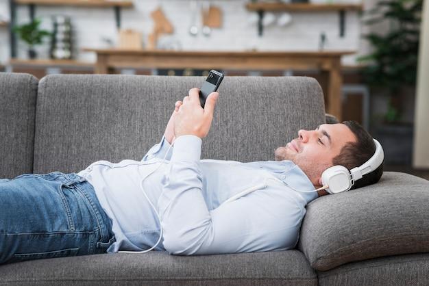 Vista frontale dell'uomo sdraiato sul divano