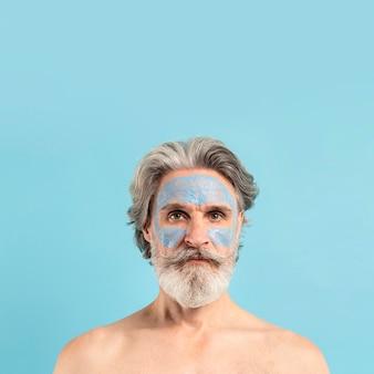 Vista frontale dell'uomo senior barbuto con la maschera