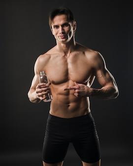 Vista frontale dell'uomo senza camicia atletico che indica alla bottiglia di acqua