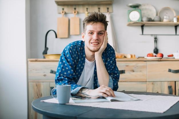 Vista frontale dell'uomo sorridente che guarda l'obbiettivo con la rivista e tazza di caffè