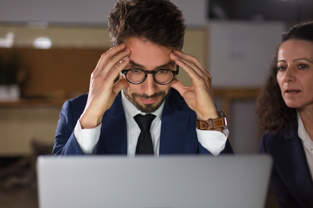 Vista frontale dell'uomo stanco in occhiali che esaminano computer portatile