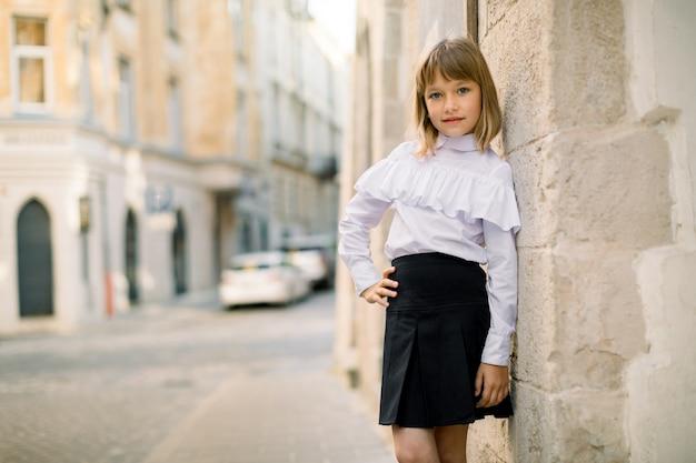 Vista frontale della bambina bionda in vestiti in bianco e nero in posa presso la città di strada sullo sfondo del muro del vecchio edificio
