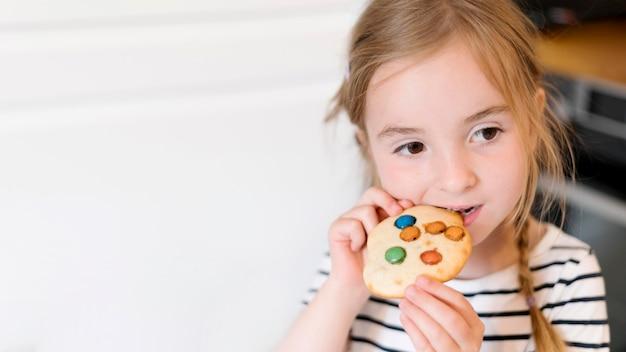 Vista frontale della bambina che mangia un biscotto