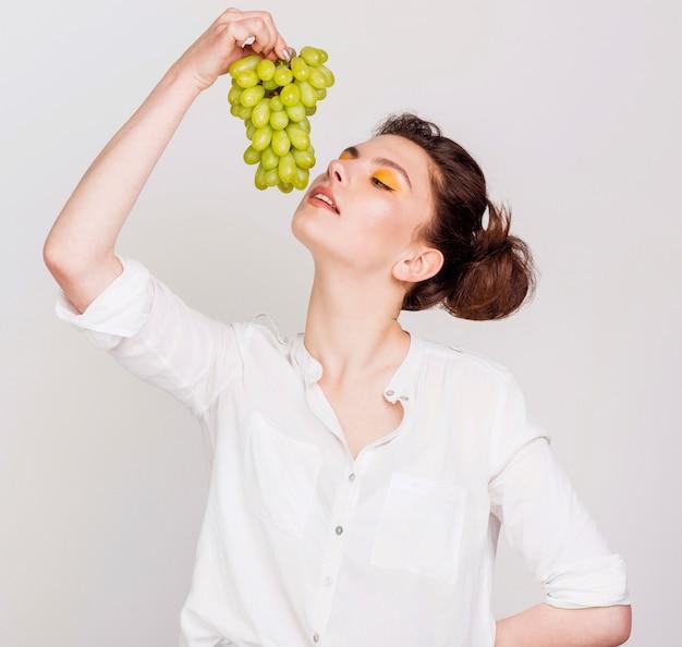 Vista frontale della bella donna con uva