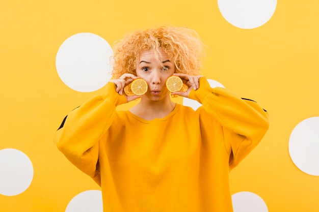 Vista frontale della bella ragazza con fette di limone
