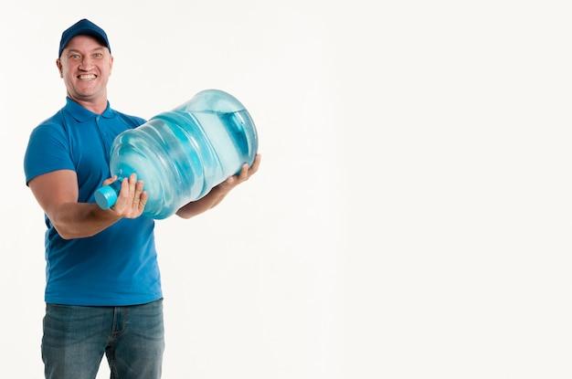 Vista frontale della bottiglia di acqua e del sorridere della tenuta del fattorino
