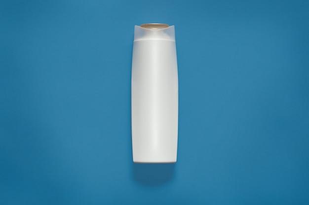 Vista frontale della bottiglia di plastica bianca in bianco dei cosmetici isolata sullo studio blu, sul contenitore cosmetico vuoto, su derisione e spazio della copia per pubblicità o testo promozionale. concetto beuity.