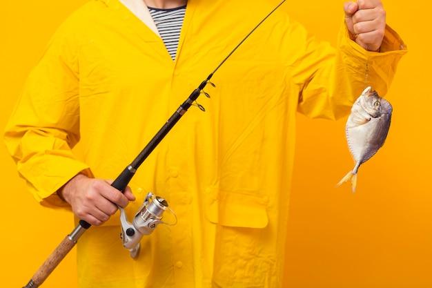 Vista frontale della canna da pesca della tenuta del pescatore con la cattura