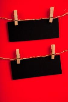 Vista frontale della carta nera su sfondo rosso con spazio di copia
