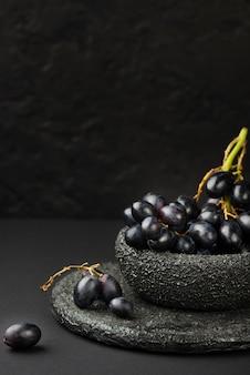 Vista frontale della ciotola con l'uva e lo spazio della copia