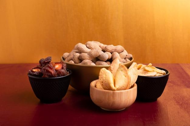 Vista frontale della ciotola di arachidi e altre prelibatezze per il nuovo anno cinese