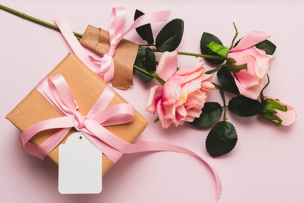 Vista frontale della confezione regalo con bouquet di rose e nastro