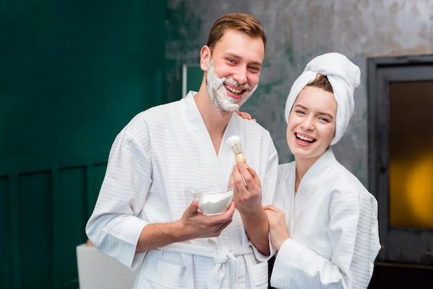 Vista frontale della coppia in accappatoi con schiuma da barba
