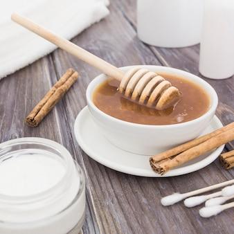 Vista frontale della crema di concetto del bagno e del cucchiaio del miele