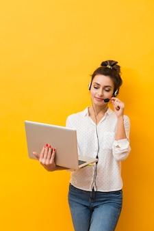 Vista frontale della cuffia avricolare da portare della donna che cattura ai clienti sul computer portatile