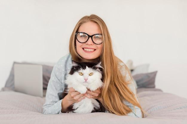 Vista frontale della donna a letto che indossa un pigiama con gatto e laptop