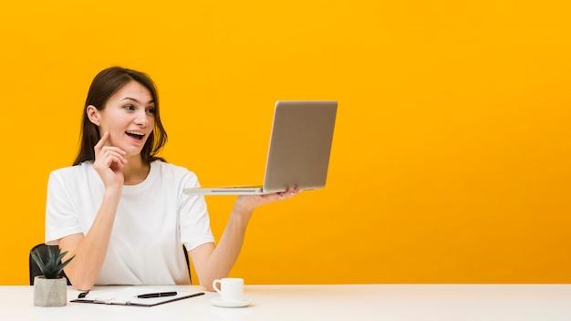 Vista frontale della donna allo scrittorio che gode di ciò che vede sul suo computer portatile con lo spazio della copia