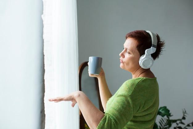 Vista frontale della donna anziana ballare e ascoltare musica