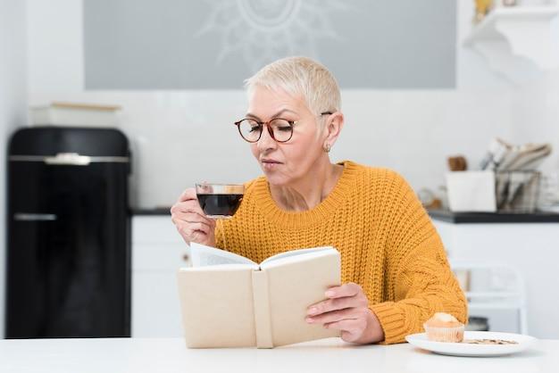 Vista frontale della donna anziana che legge un libro e che tiene la tazza di caffè