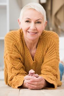 Vista frontale della donna anziana che posa e che sorride meravigliosamente