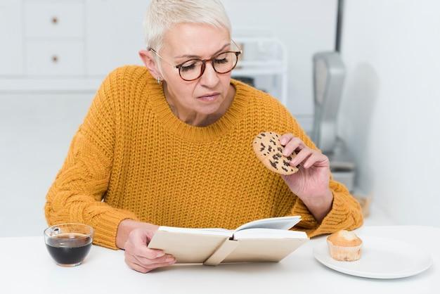Vista frontale della donna anziana che tiene grande biscotto e libro di lettura