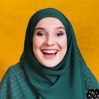 Vista frontale della donna araba allegra sul contesto giallo