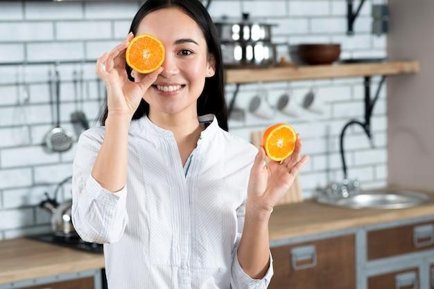 Vista frontale della donna asiatica che copre il suo un occhio con fetta d'arancia in cucina