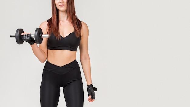 Vista frontale della donna atletica che si esercita con il peso