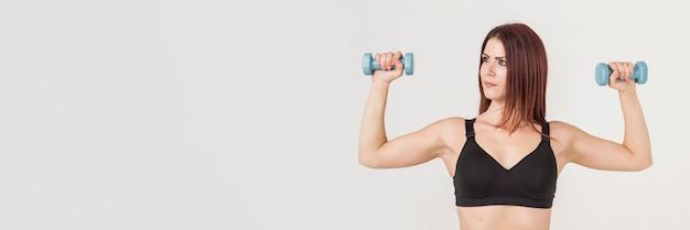 Vista frontale della donna atletica che sostiene i pesi e che mostra il suo bicipite