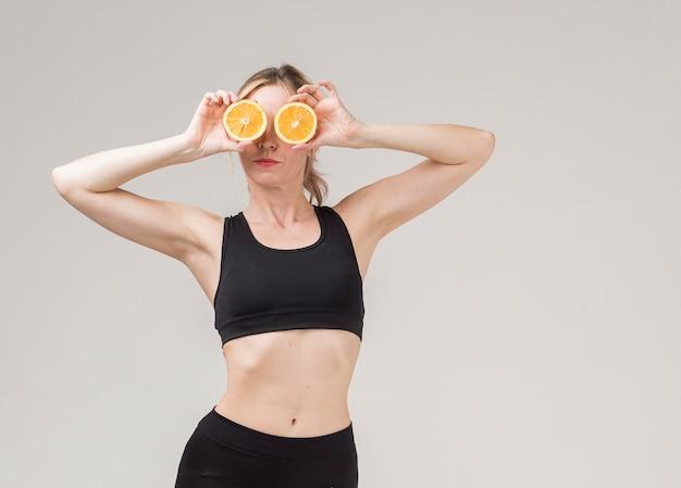 Vista frontale della donna atletica che tiene i halfs arancioni sopra i suoi occhi