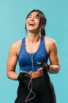 Vista frontale della donna atletica in attrezzatura della palestra che gode della musica