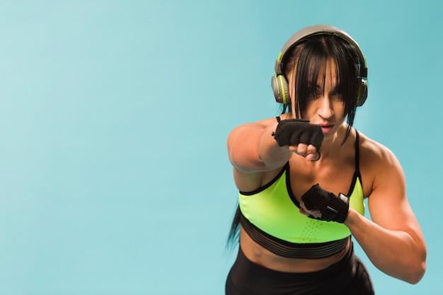 Vista frontale della donna atletica nella perforazione dell'attrezzatura della palestra