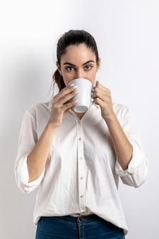 Vista frontale della donna che beve dalla tazza