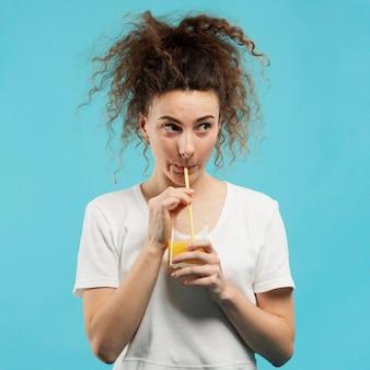 Vista frontale della donna che beve il succo