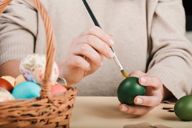 Vista frontale della donna che decora le uova di pasqua