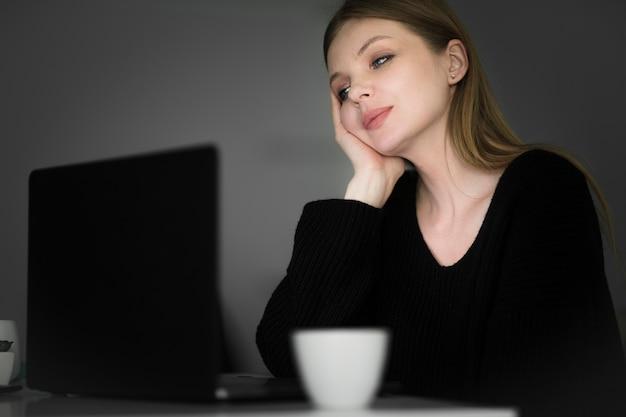 Vista frontale della donna che esamina computer portatile